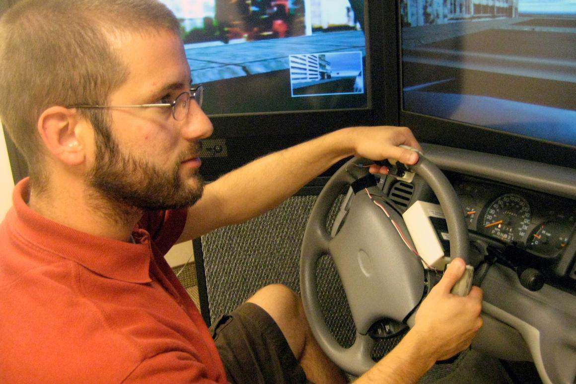University of Utah psychology doctoral student, Nate Medeiros-Ward, operates a driving simulator with a steering wheel equipped with two touch devices that pull the skin on his index fingertips left or right (Image: Justin Lukas, University of Utah)