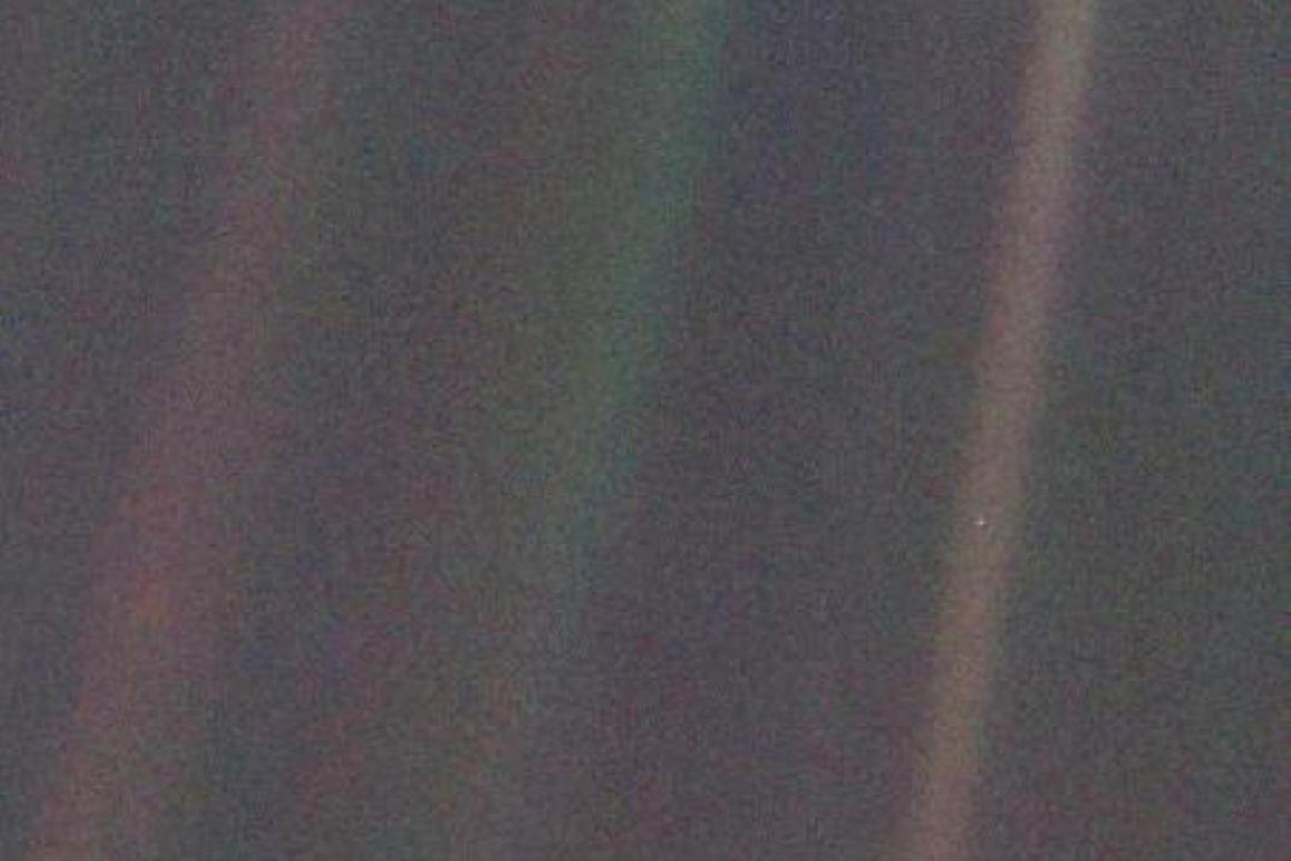 Voyager 1's iconic pale blue dot, with Earth featured as a tiny spec in the light band on the right of the image