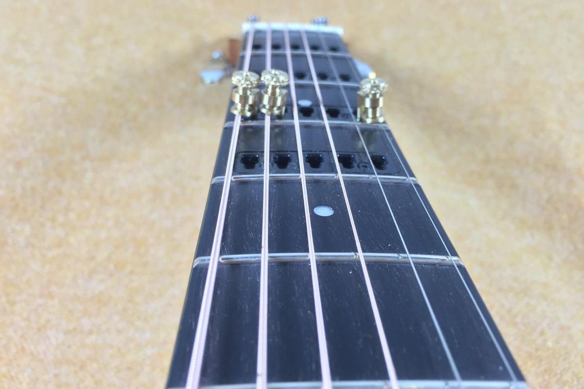 Metal capos are locked in position on individual strings of the Gillis Capo Guitar