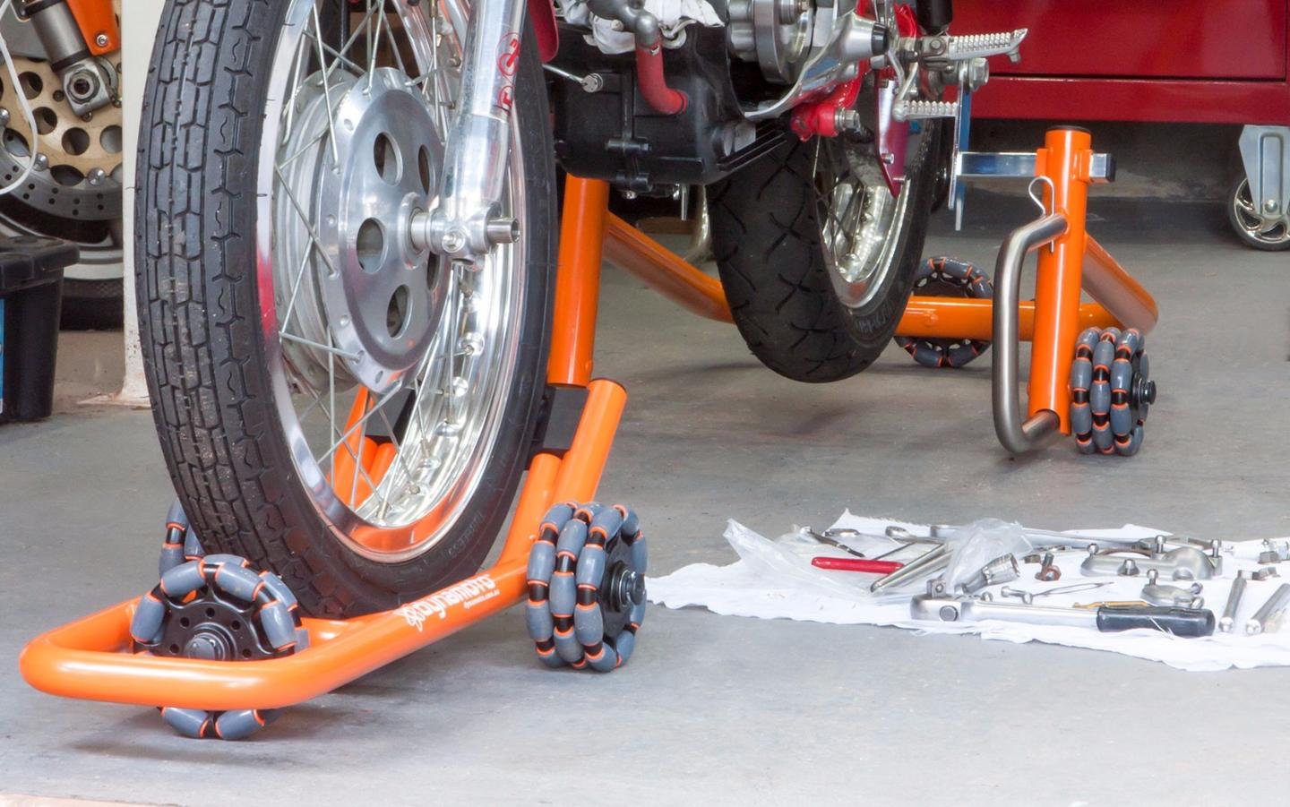Dynamoto's front stand scoots under the front wheel to lift the bike without the need for spools