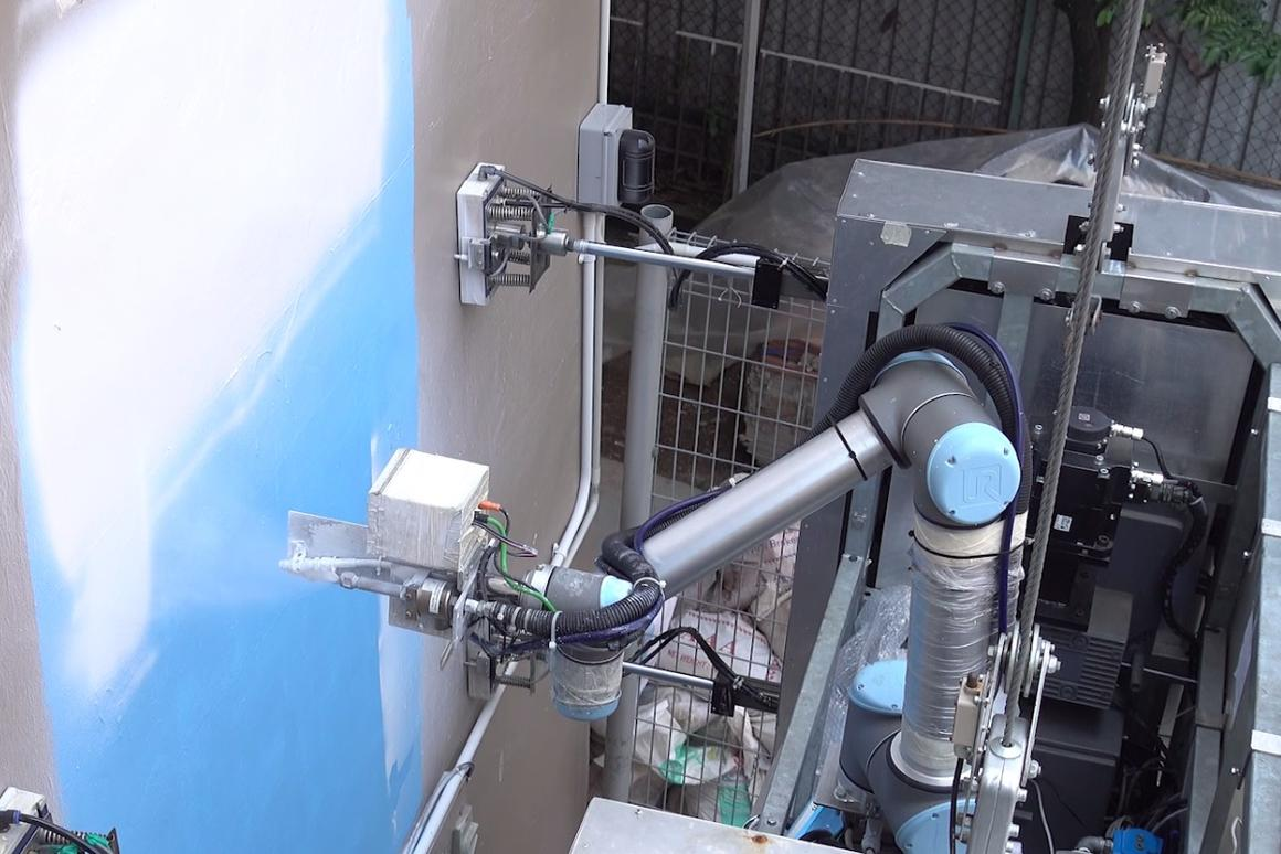 OutoBot applies white paint to an industrial building