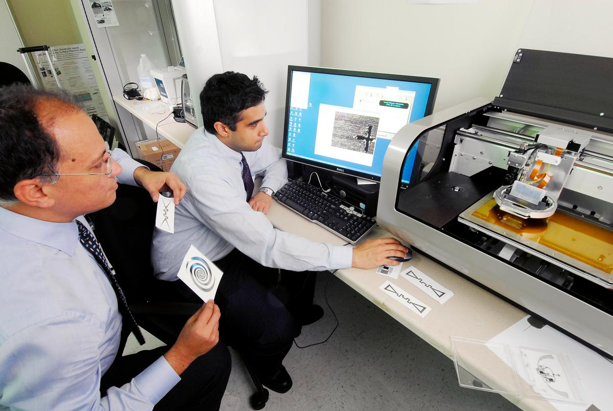 Georgia Tech School of Electrical and Computer Engineering professor Manos Tentzeris (left) and Ph.D. candidate Rushi Vyas (right) work with an inkjet manufacturing system (Photo: Greg Meek, Georgia Tech)