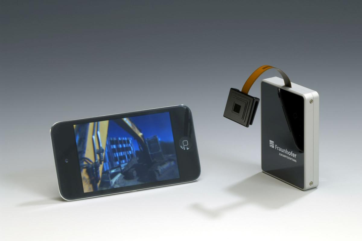 The facetVISION camera (on ribbon cable) alongside a smartphone