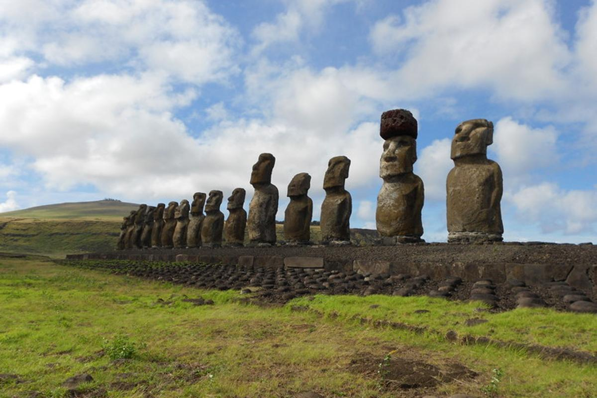 A row of moai statues on Easter Island, with the second from the right  wearing a pukao (red stone hat)