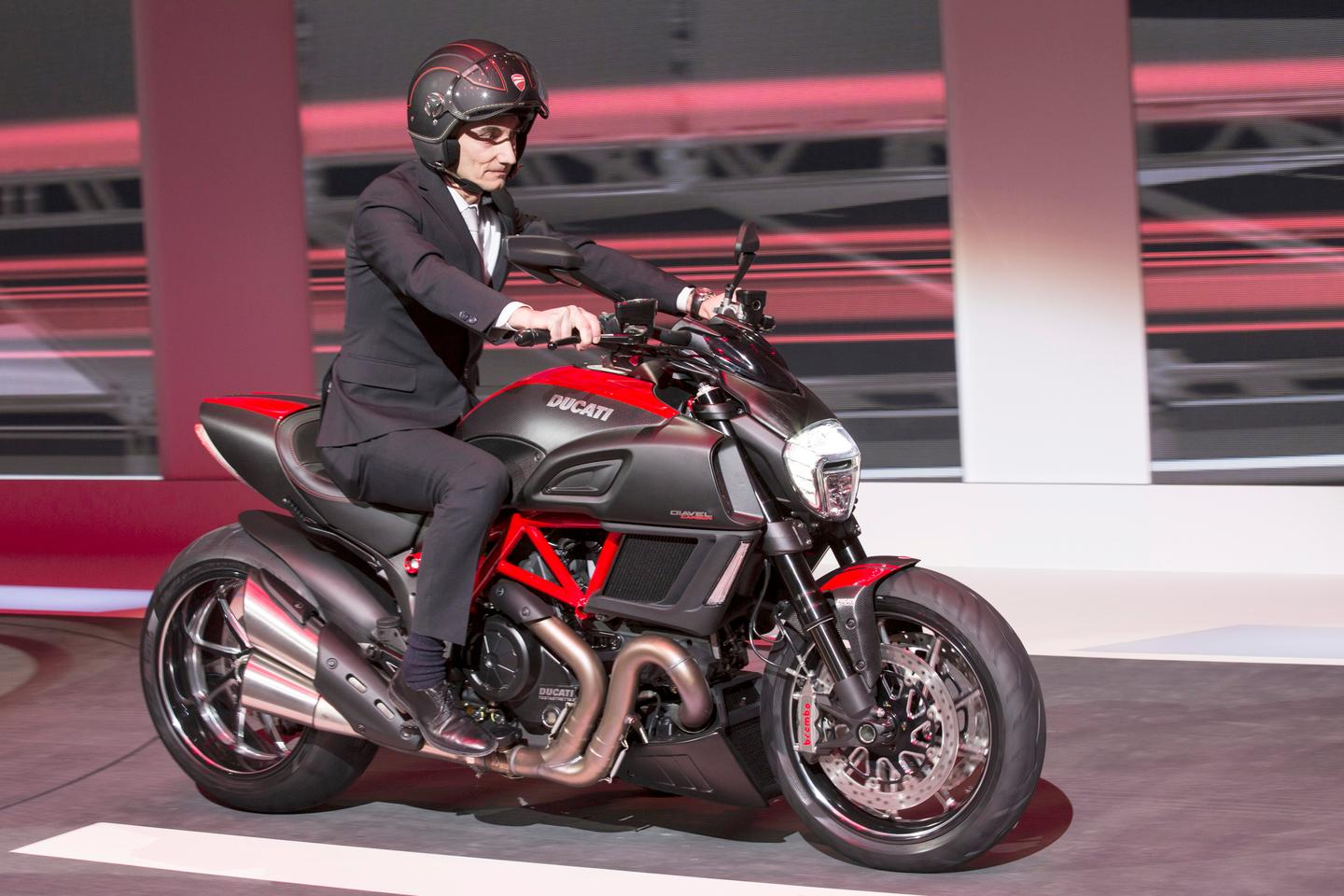 Ducati's CEO Claudio Domenicali rides the Ducati Diavel Carbon onto the stage in Geneva, putting the marque on display to the world's automotive press