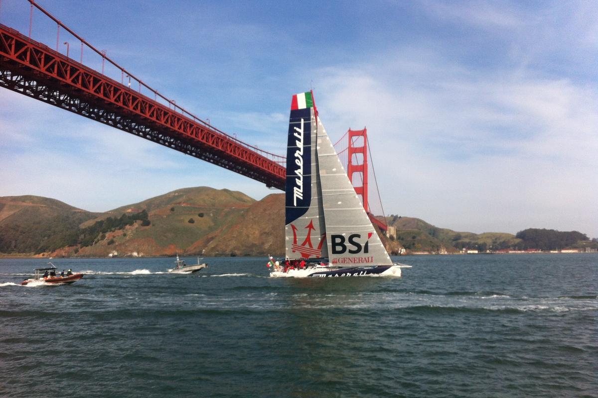 The Maserati monohull crosses the finish line under the Golden Gate Bridge