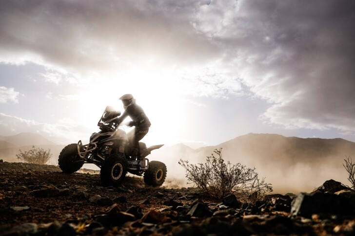 Simon Vitse and his BBR Mercier Racing quad are kissed by beautiful sunlight on dust outside Neom