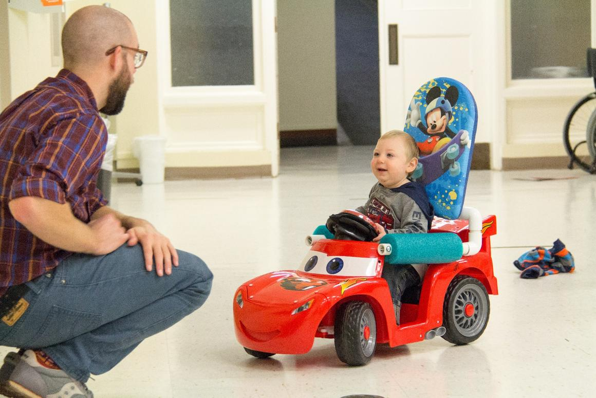 Researcher Sam Logan, leader of theGo Baby Go program at Oregon State University, with a youngster driving a Go Baby Go modified toy car
