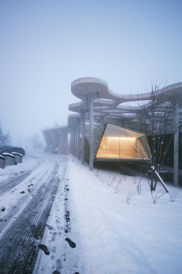 """The """"Suspended Forest"""" cabin hangs from a large overhead concrete structure, allowing the dwelling to hover above the snow-covered landscape"""