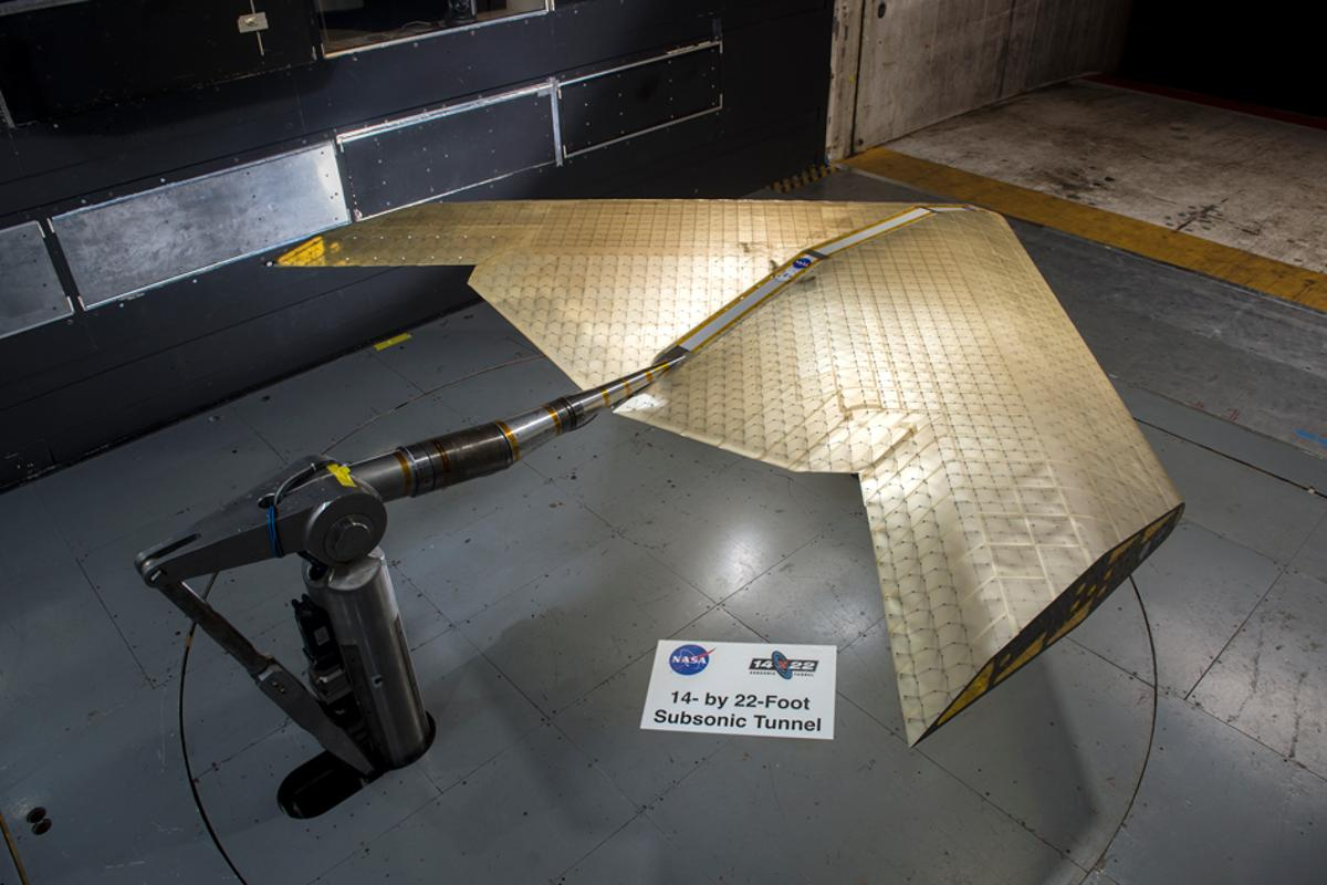 Wing assembly is seen under construction, assembled from hundreds of identical subunits. The wing was tested in a NASA wind tunnel