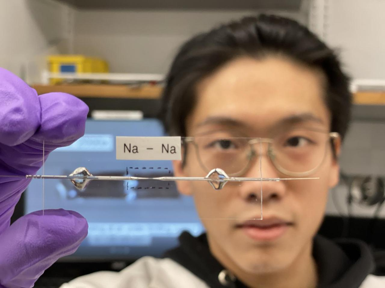 Researcher at Washington University in St Louis Bingyuan Ma holds up a transparent capillary cell, used to optimize the performance of an experimental sodium battery