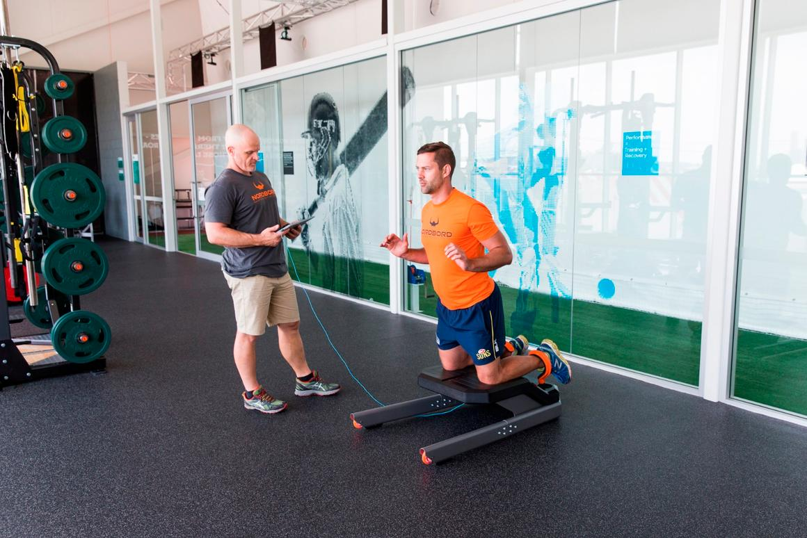 A trainer and athlete use the Nordbord to measure hamstring strength