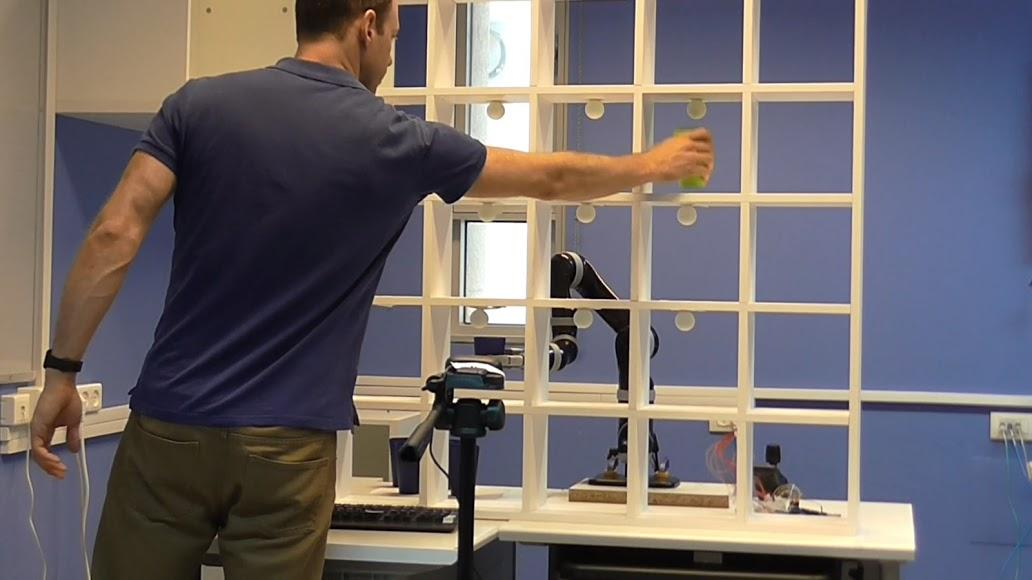 A test subject plays tic tac toe against the robotic arm