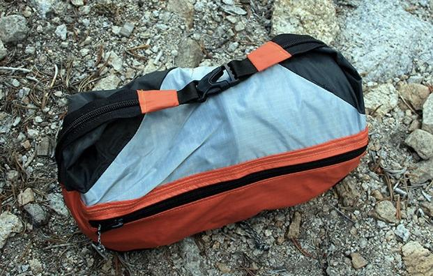 The Grub Hub Cirque folds up into a small carry case that holds a backpacking stove, pot fuel and cooking tools