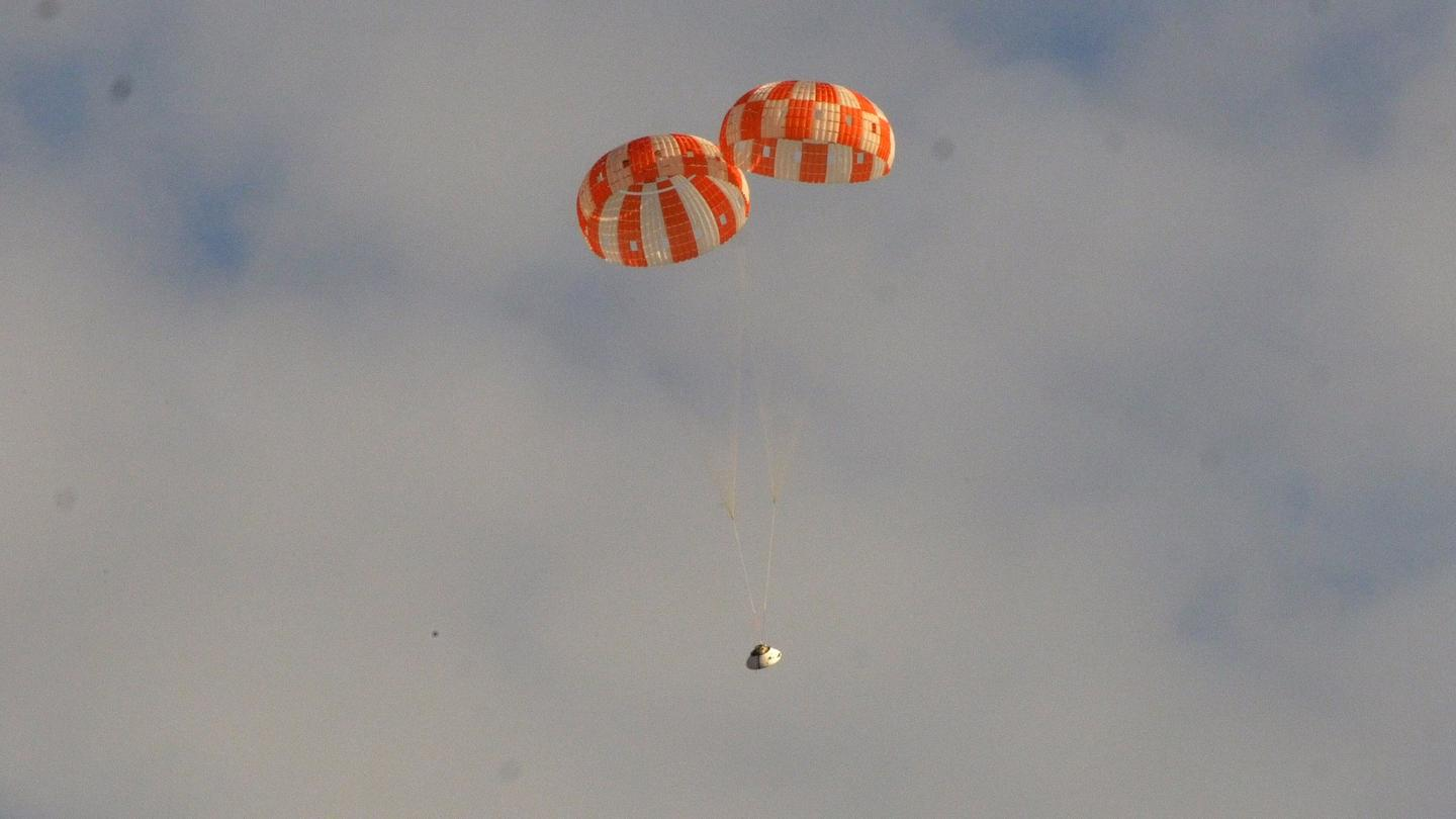 A mock Orion spacecraft descends under two main stage parachutes