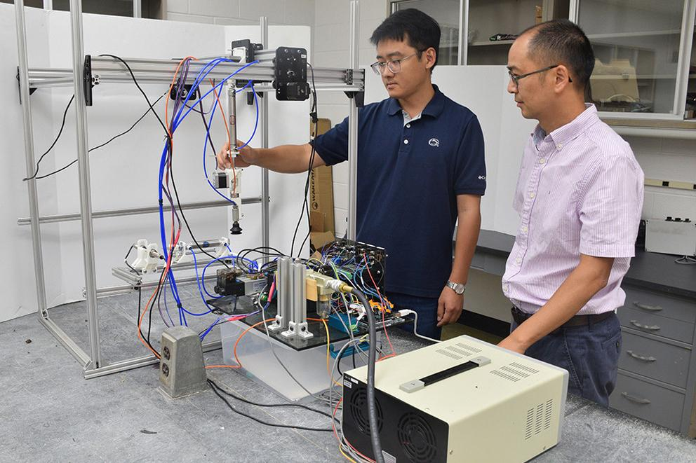 Asst. Prof. Long He (right) and visiting doctoral student Mingsen Huang with the prototype robot