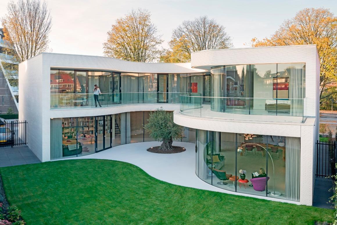 Casa Kwantes'expansive glazed facadecurves around an olive tree