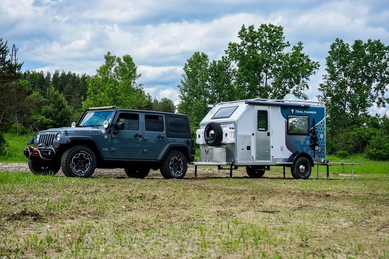 A Jeep Wrangler Unlimited tows the Trail Marker Sequoia to camp