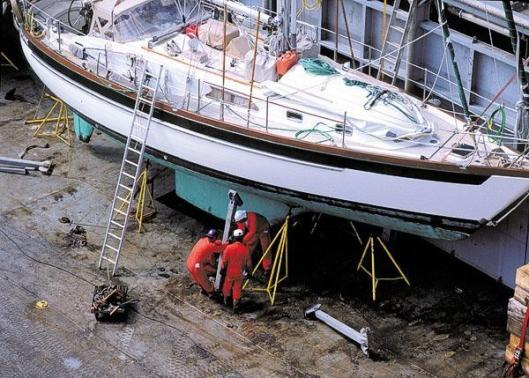 Dockwise technicians securing a yacht for transport.