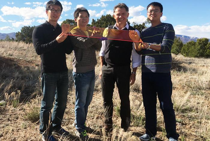 The researchers, (from left) Jaehoon Lim, Kaifeng Wu, Victor Klimov and Hongbo Li, holding a plane of their quantum dot LSC glass