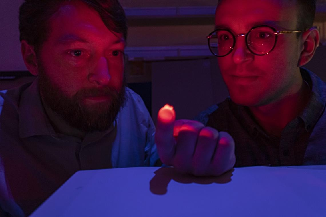 Philipp Gutruf (left) and Jokubas Ausra demonstrate how the device is able to transmit light through biological tissue