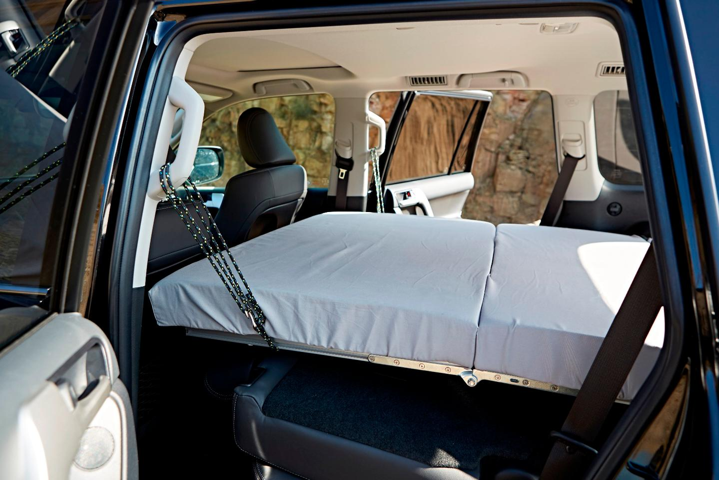 The fold-out bed is supported by straps around the grab handles