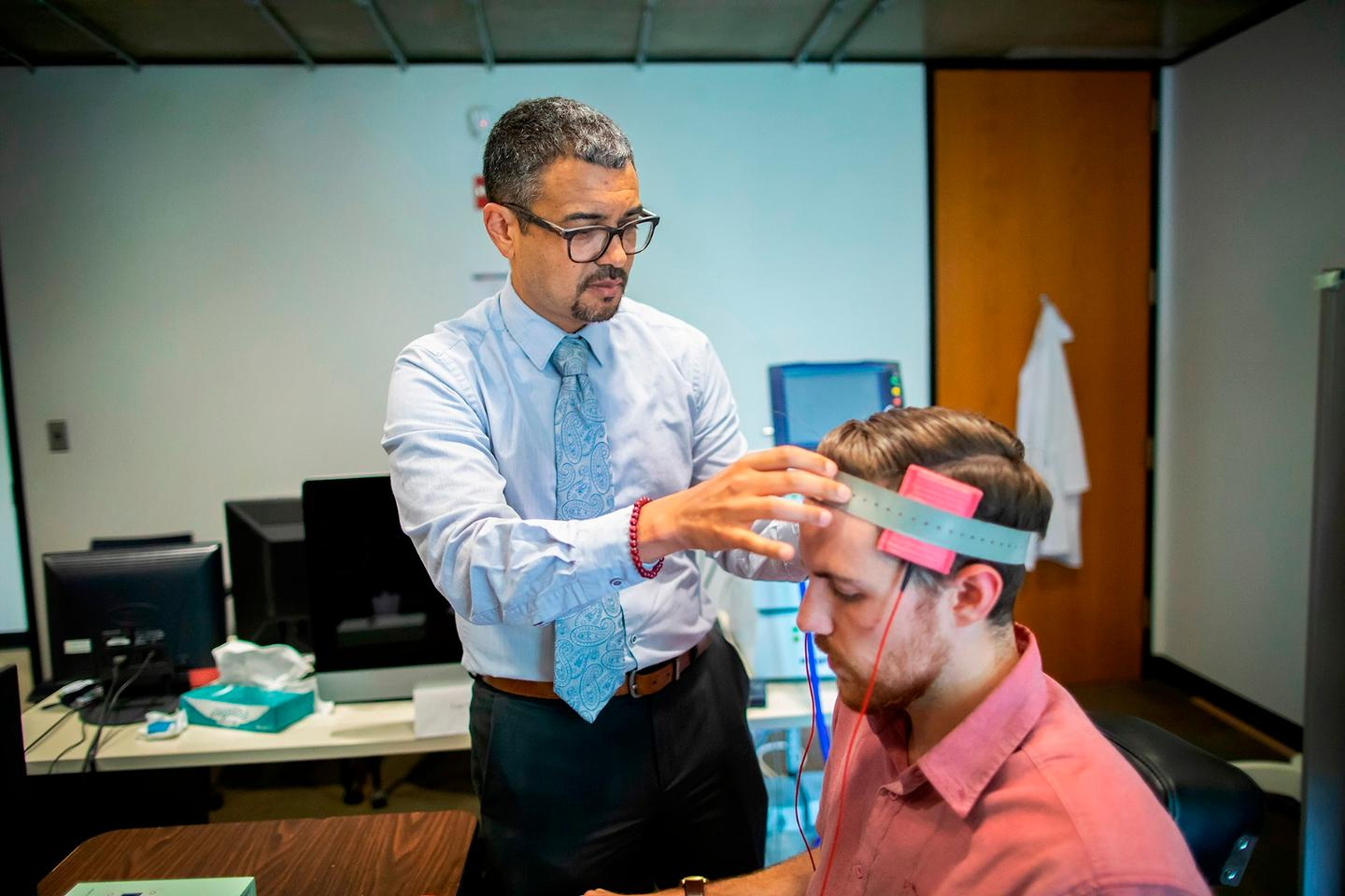 Roy Hamilton of Penn Medicine was part of a research team that studied whether a minimally invasive brain stimulation, similar to what he's demonstrating in this photo, can reduce someone's intent to commit a violent crime