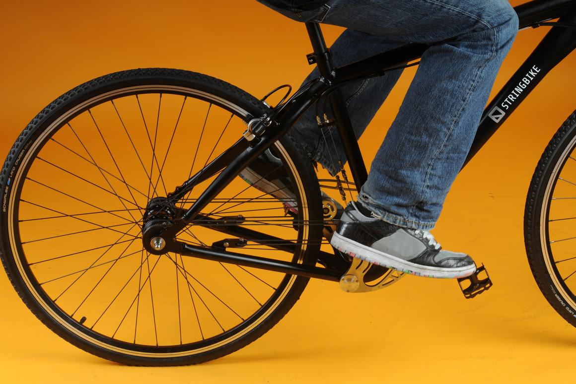 When force is applied to the pedal, the stainless steel, triangular-shaped swinging mechanism pulls on the rope and rotates a drum on the rear wheel to give forward momentum