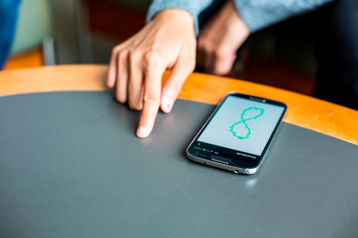 A FingerIO-equipped phone tracks a user's finger as it draws a figure 8 on the table