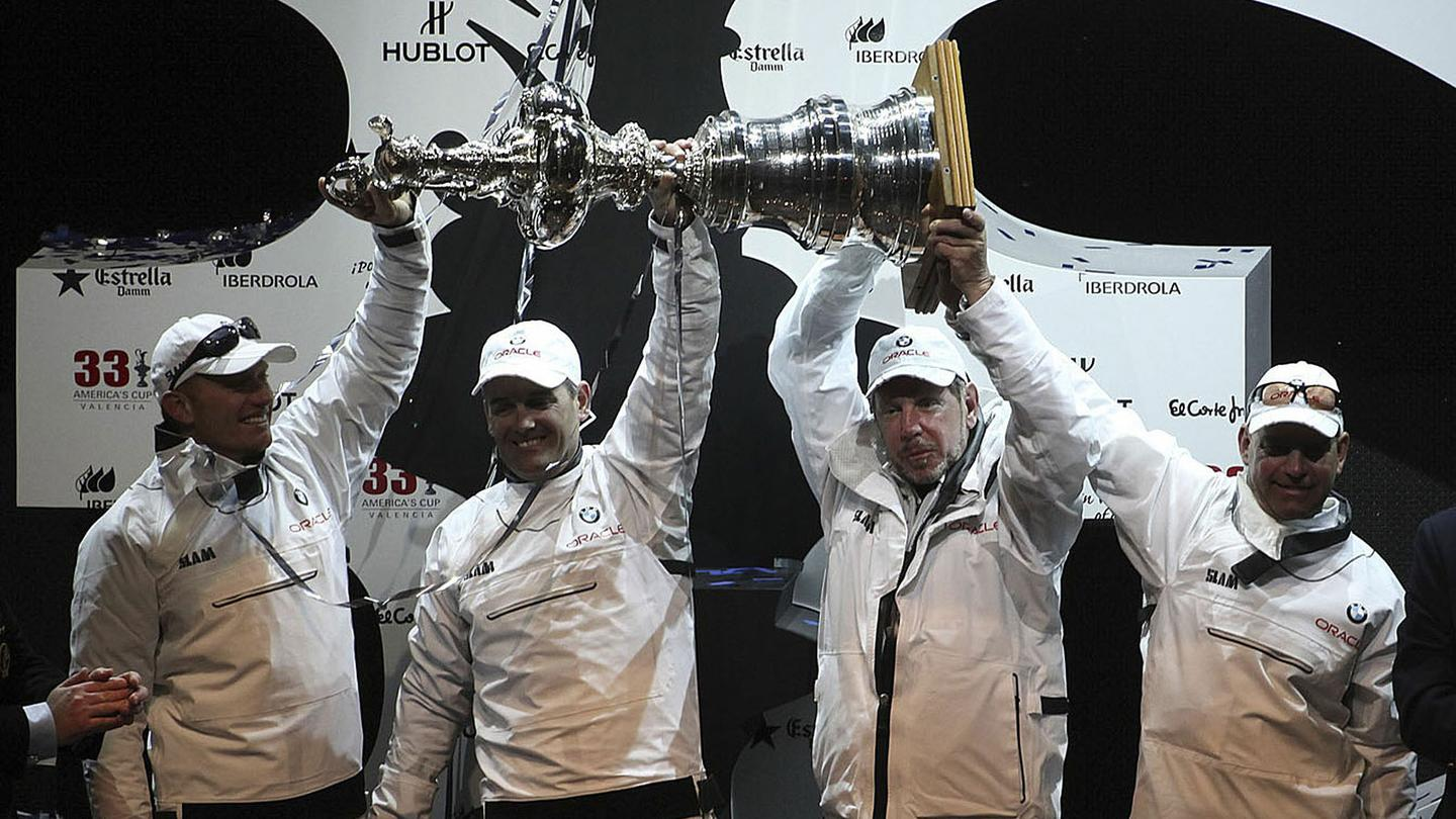 Team BMW Oracle with Larry Ellison at the helm hold the trophy aloft