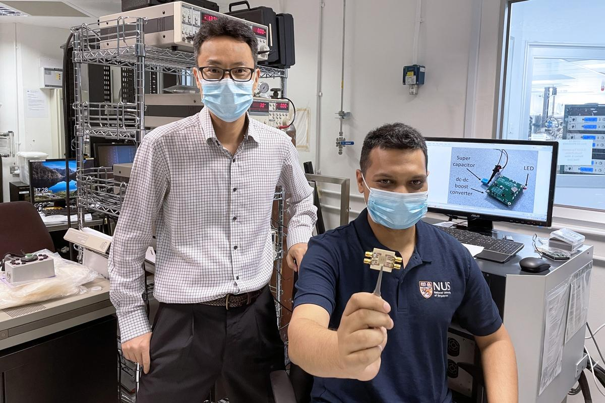 Researchers hold up a chip featuring an array of tiny devices called spin-torque oscillators, which were able to produce power for an LED