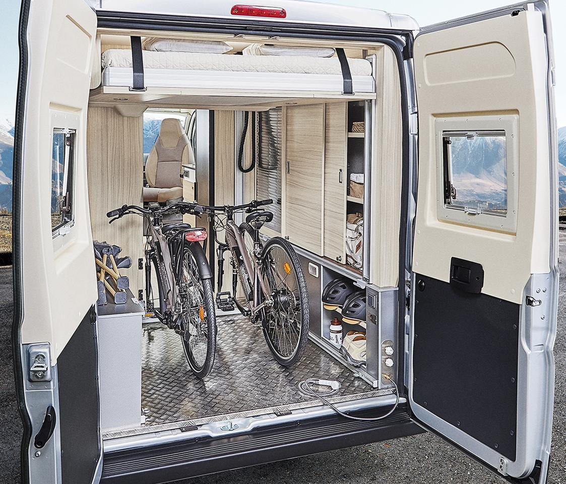 The lower bed removes and the upper bed lifts electrically to clear out a full garage for bikes and other gear