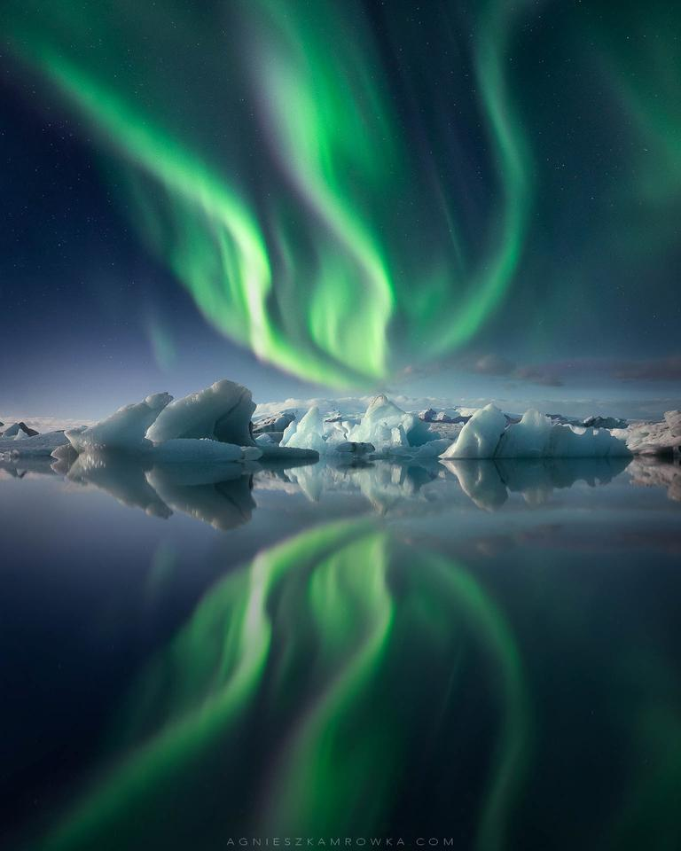 Convergence by Agnieszka Mrowka, taken at Jökulsárlón in Iceland. The aurora is mirrored beautifully in the still waters.