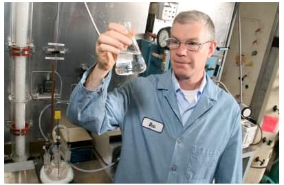 Chemist Robert Perry checks a flask containing an ingredient similar to those found in shampoos that shows promise for capturing carbon dioxide (Photo: GE Global Research)