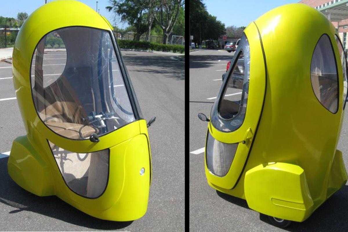 The Eggasus is a three-wheeled electric vehicle fitted with an electric hub motor, enclosed cab, tinted windows, a seat, and instrument display panel