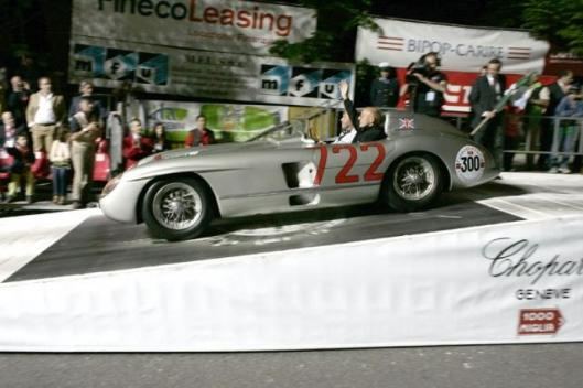 "Sir Stirling drove the ""722"" off the ramp at 09:40 p.m. in front of a cheering crowd and changed seats with Jochen Mass after a farewell drive through Brescia."