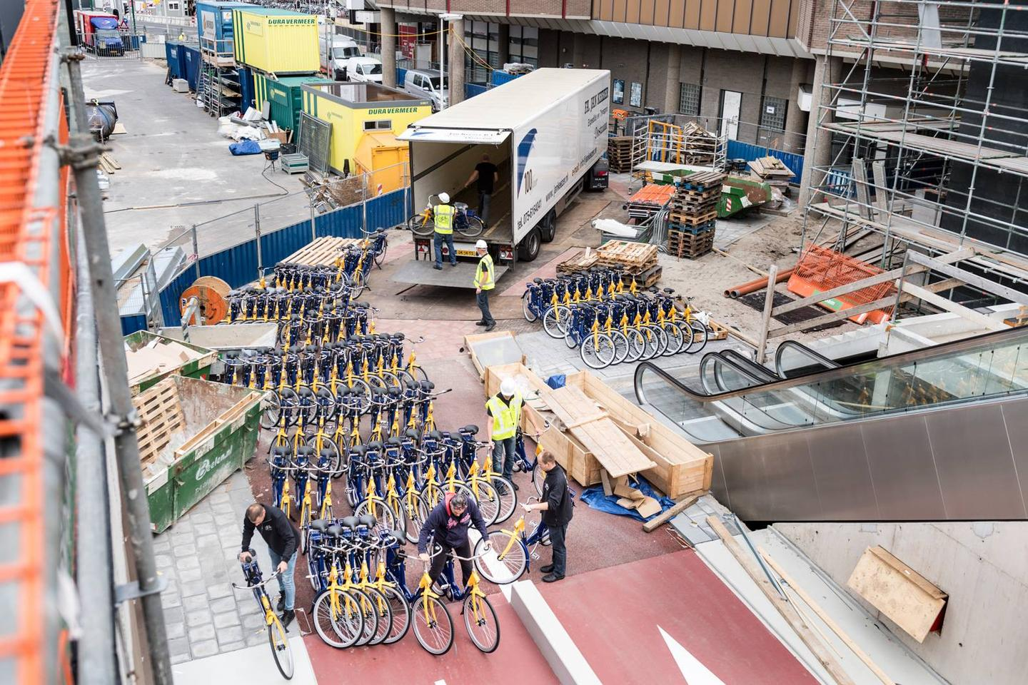 Workmen start moving 700 public hire bicycles into the Stationsplein Bicycle Parking facility in Utrecht
