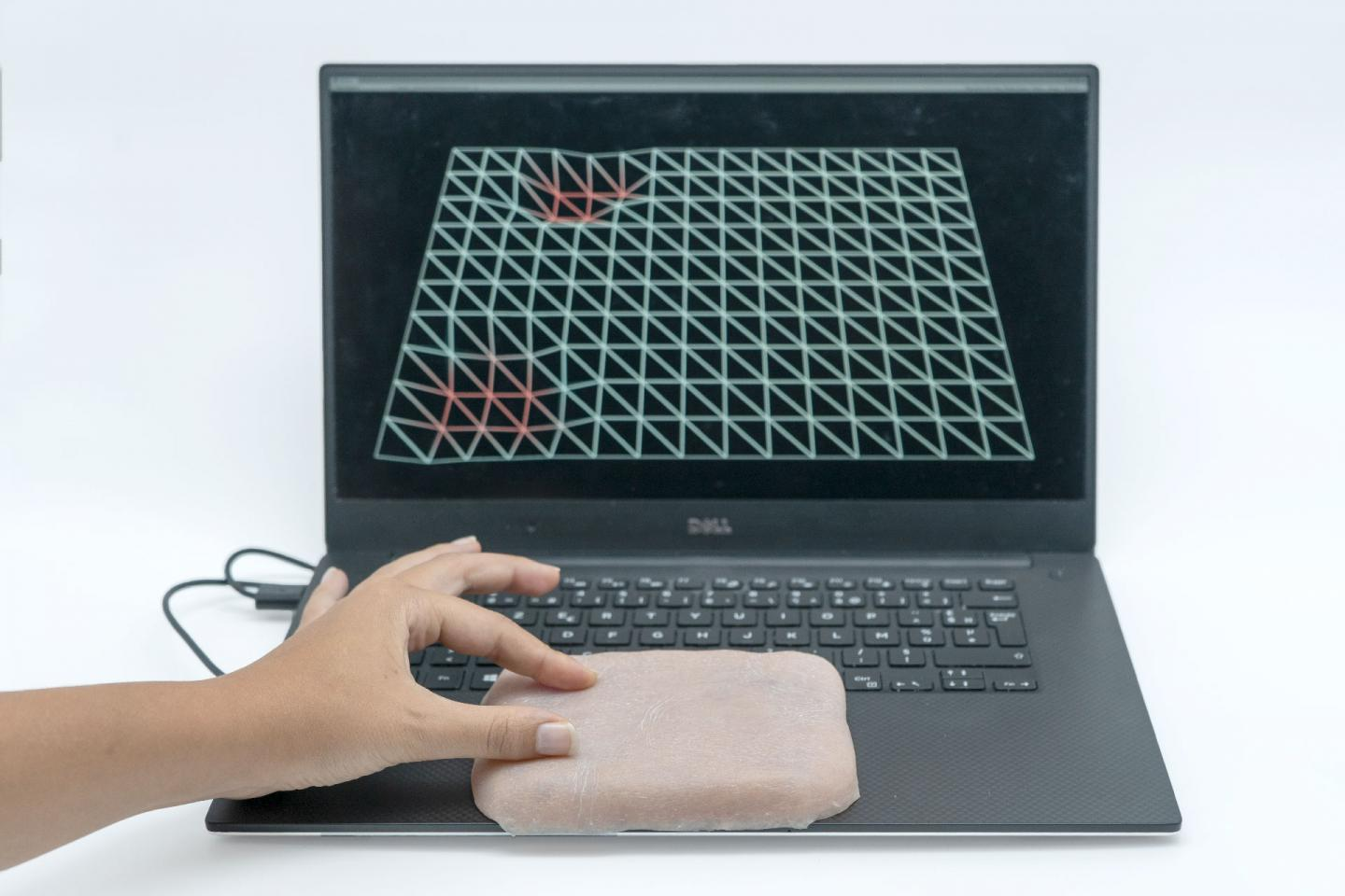 A Skin-On-equipped touchpad tracks the pressure and location of a user's fingertips