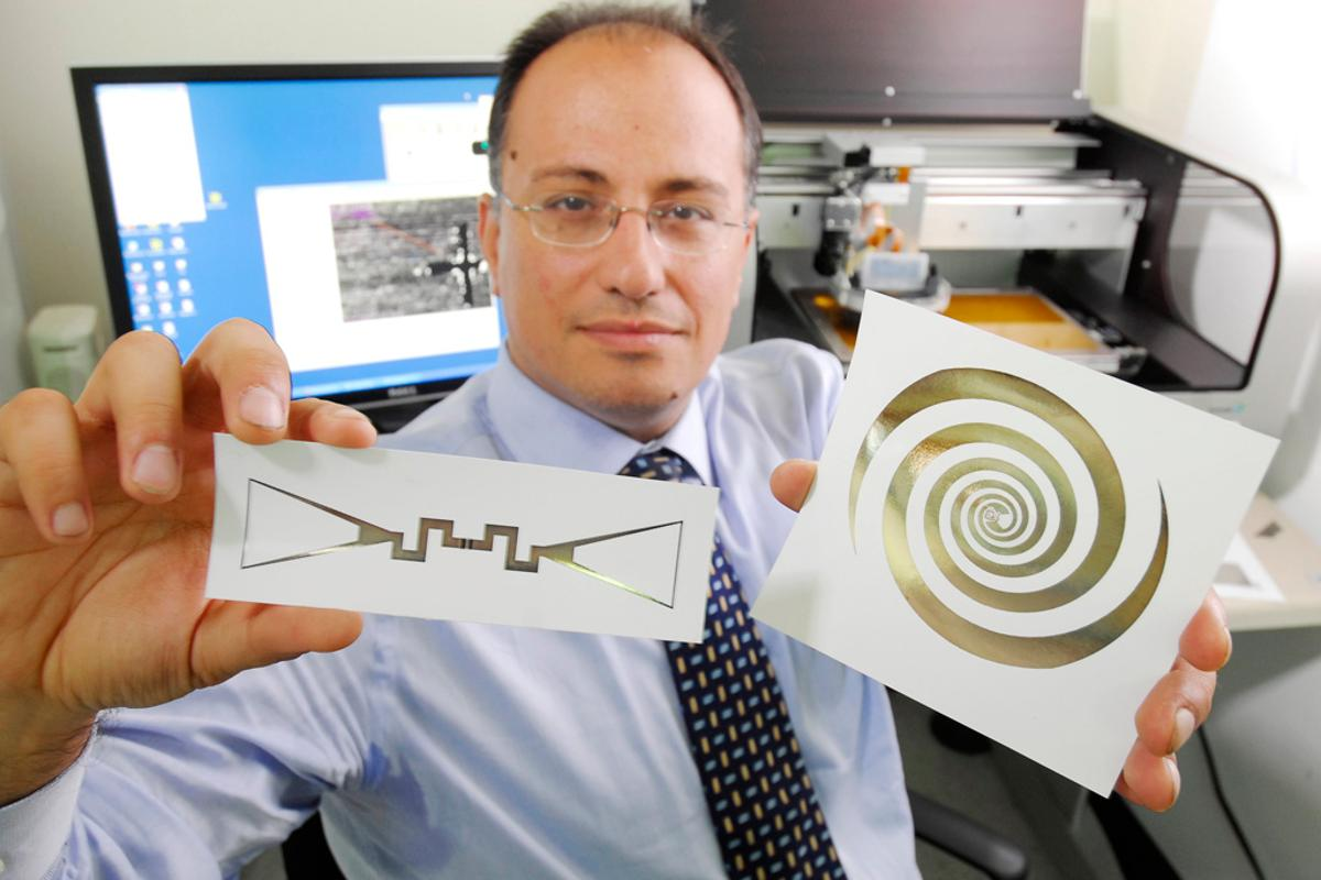 Manos Tentzeris holds a sensor (left) and an ultra-broadband spiral antenna for wearable energy-scavenging applications that were both printed on paper using inkjet technology (Image: Gary Meek)
