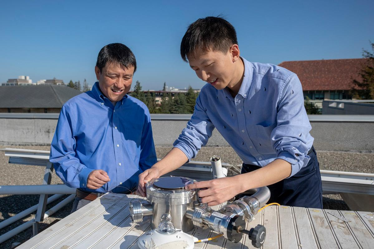 Professor Shanhui Fan and postdoctoral scholar Wei Li with a prototype device used to test a system that passively cools a building and generates electricity from solar