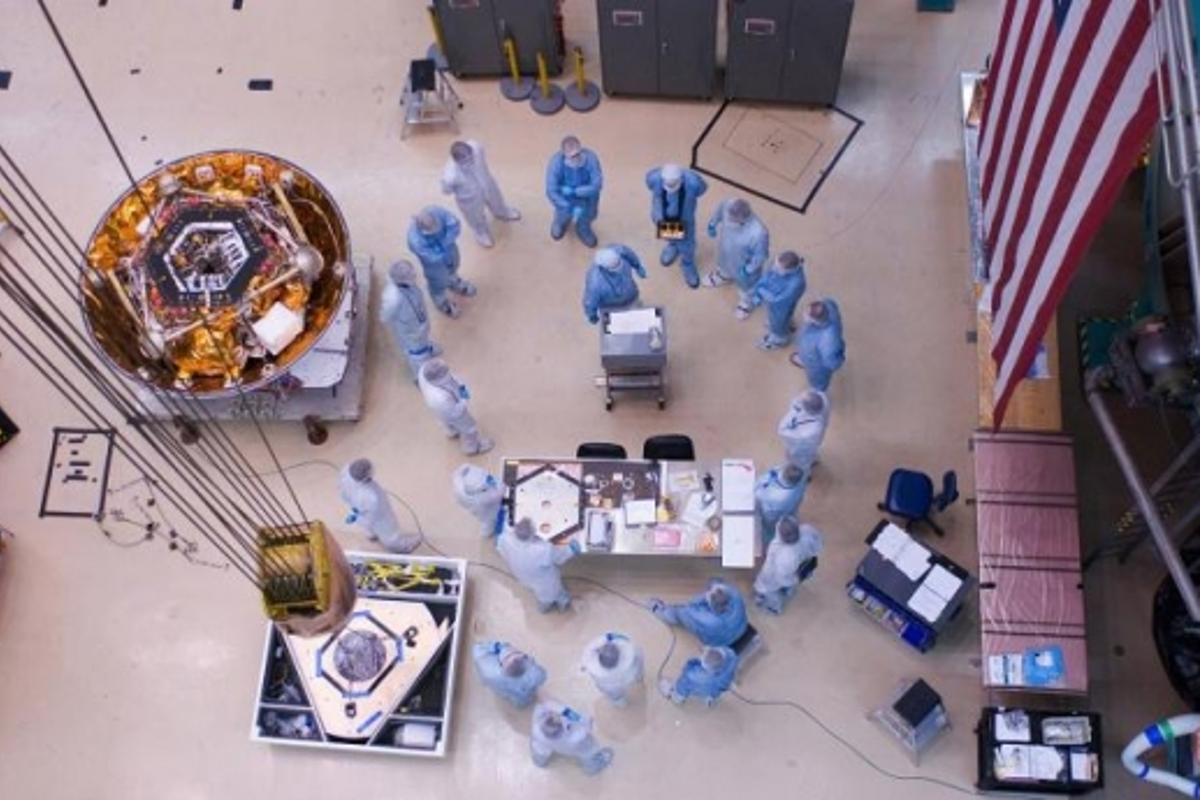 Spacecraft specialists huddle to discuss the critical lift of NASA's Phoenix Mars Lander into a thermal vacuum chamber. In December 2006, the spacecraft was in a cruse configuration prior to going into environmental testing at a Lockheed Martin Space Syst