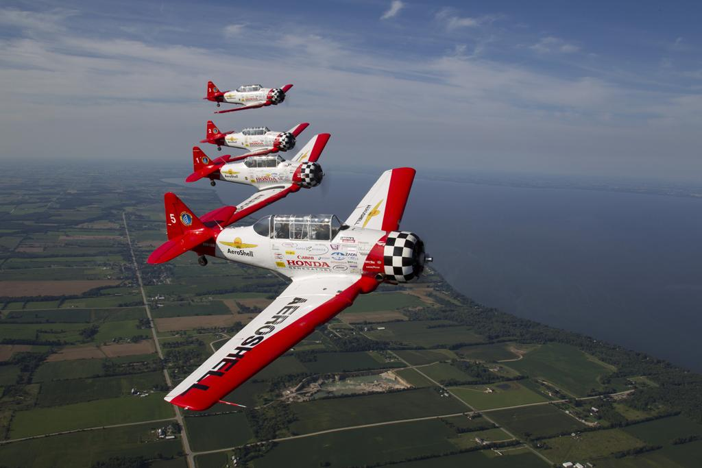 The AeroShell team in formation over Oshkosh (EAA photo/Amy Gesch)
