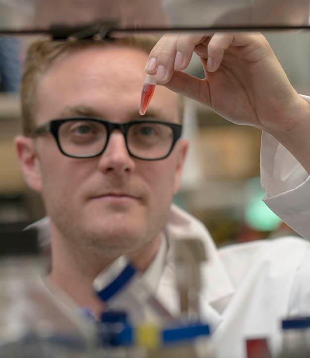 McMaster University chemical biology graduate student Andrew King examines a chemical used in drug discovery research (Photo: JD Howell)
