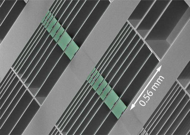 An array of the optomechanical accelerometers on the surface of a microchip – the proof masses are highlighted in green