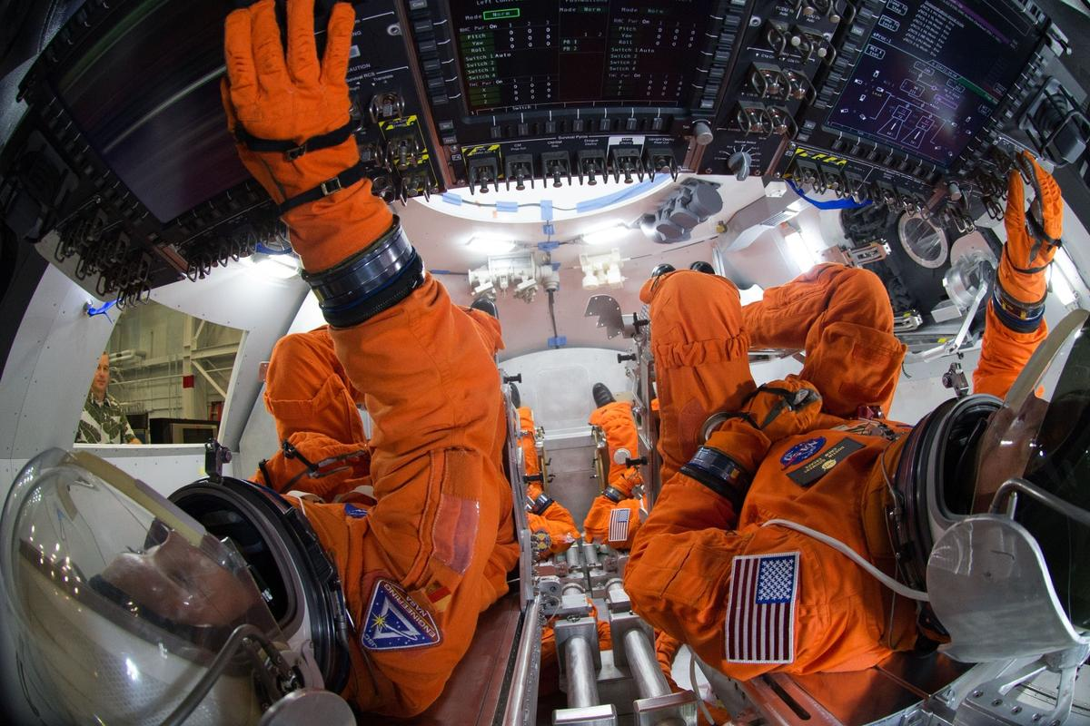 Spacesuit engineers demonstrating crew arrangement in the Orion capsule