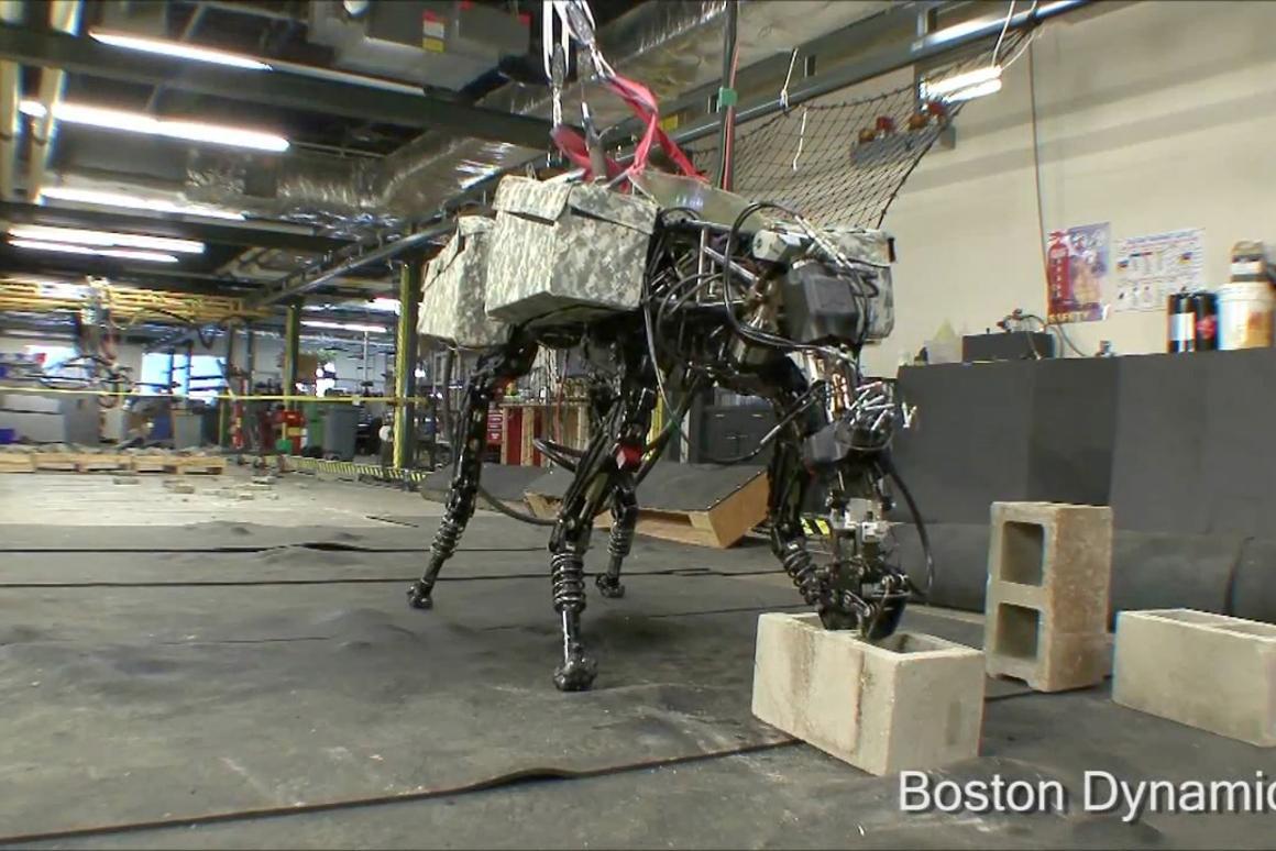 Boston Dynamics' quadruped robot BigDog grabs a cinder block from the floor using its new arm attachment