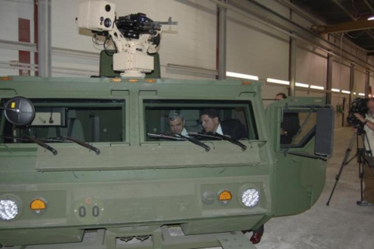 Steve Nimmer, of Oshkosh Truck Corporation, (right) demonstrates the operation of the HEMTT A3 all-composite cab to Rhode Island Senator Jack Reed (D-RI).