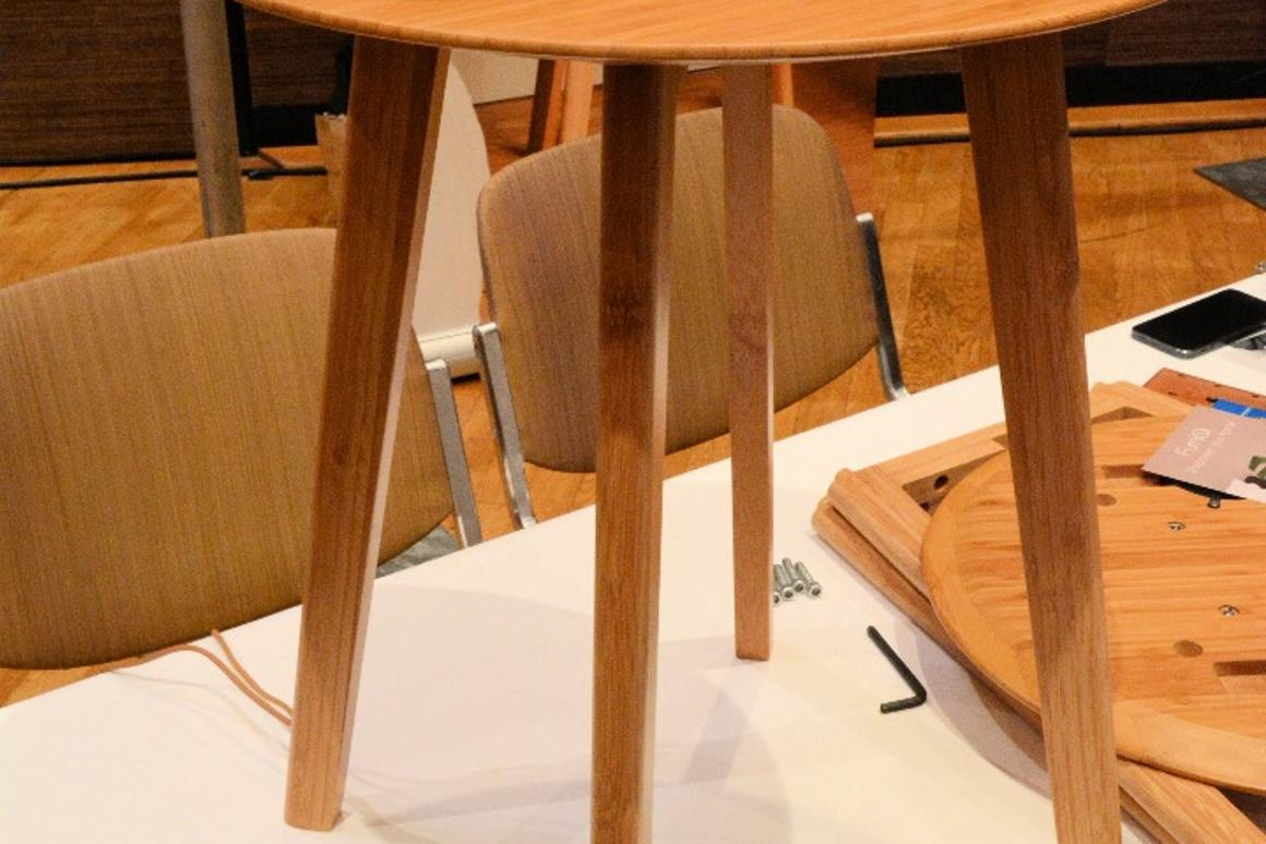 A fully-assembled FurniQi side table with Qi-compatible devices on top