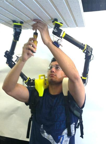 Researcher demonstrates the operation of the robot arms when installing ceiling panels in an airplane