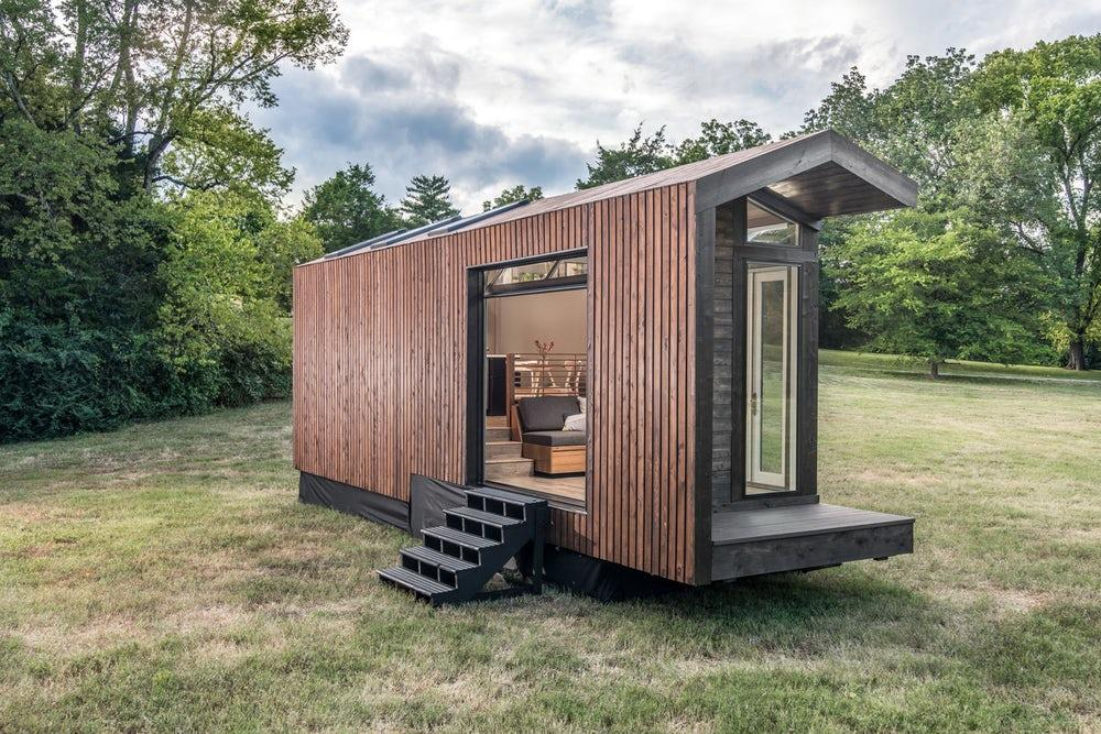 The Orchid Tiny House's trailer wheels are hiddenbehind a cover